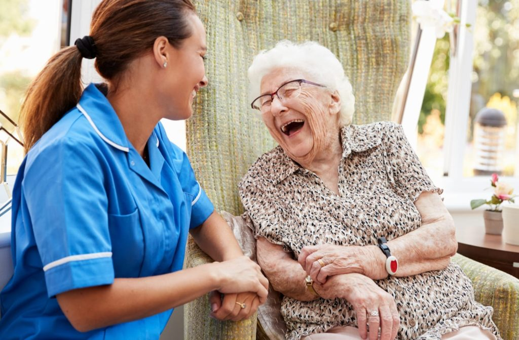 A senior woman shares a big laugh with a friendly staffer at a long-term care facility